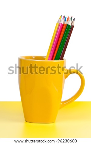 Multicolor pencils in a bright yellow cup