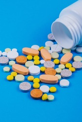 Multicolor pills and tablets spilling out from plastic pill bottle on blue. Various treatments mixed. Variety of pills and medication. Close up. Macro. Medical concept.