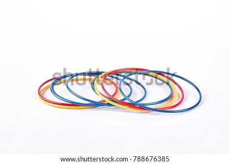Multicolor plastic bangles on white background. Set of multicolored wrist bands on white background. Female hands accessories. #788676385
