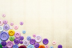 Multicolor sewing buttons on the cloth fabric background