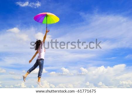 Multicolor umbrella woman jump to sky