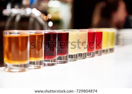 Multicolored alcoholic shots on the bar counter #729804874