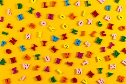 Multicolored alphabet background. Colorful letters of the English alphabet are scattered on yellow background. The concept of education in kindergarten and school. Learning the alphabet. Flat Lay