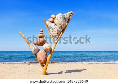 Multicolored balanced stones on an wooden snags, on a blue sky and sea background. Concept of harmony and balance.