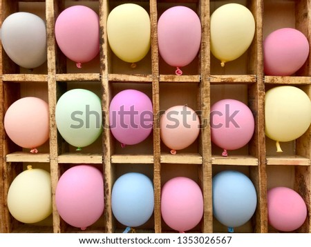 Multicolored balloons are placed in wooden groove squares.darts balloon game.happy Childhood background.colorful  backdrop.
