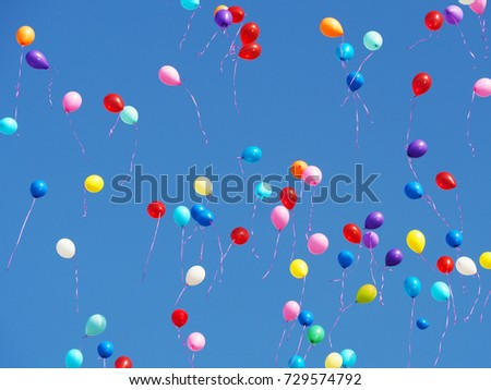Multicolored balloons filled with helium in the blue cloudless sky. Flying multicolor balls
