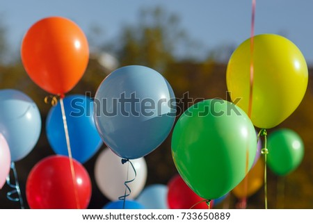 Multicolored balloons filled with helium in the blue sky. Flying multicolor balls #733650889