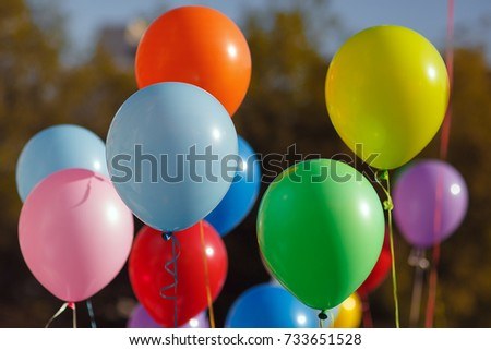Multicolored balloons filled with helium in the blue sky. Flying multicolor balls #733651528