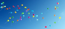 multicolored balloons fly through the blue sky