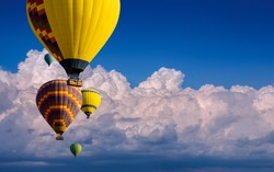Multicolored balloons on a blue sky with clouds with place for your text. Romantic weekend in the seventh heaven, a tourist poster about vivid dreams or an unusual journey - balloon flight.