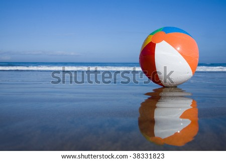 Multicolored beachball on the beach with reflection