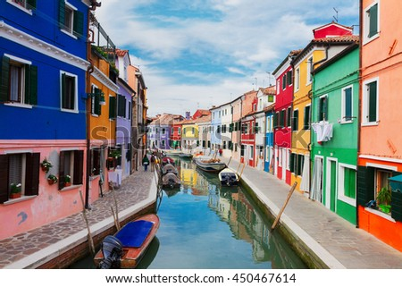 multicolored bright houses over canal with boats of Burano island, Venice, Italy #450467614