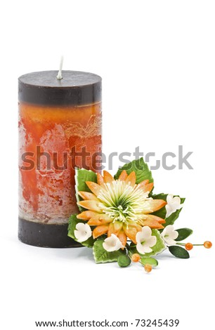 Multicolored candle arranged with beautiful flowers as a home and spa decoration