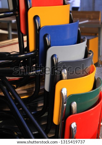 multicolored chairs piled up in front of a restaurant