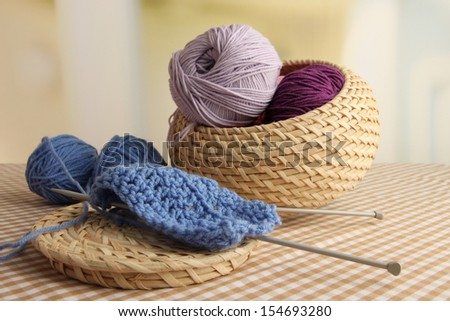 Multicolored clews in wicker basket with needles closeup