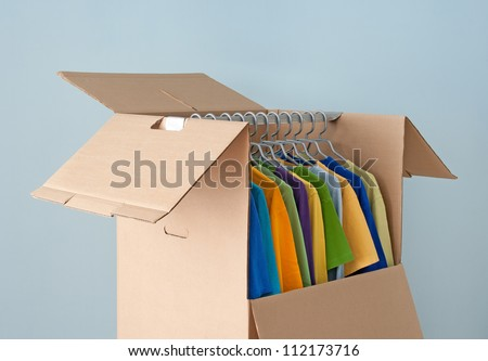 Multicolored clothes hanging in a wardrobe box, prepared for moving.
