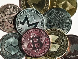 multicolored coins cryptocurrencies bitcoin Ethereum and others close up on a light background top view