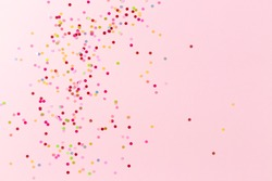 Multicolored confetti on pink background. Festive banner for text. Ready layout for designers.