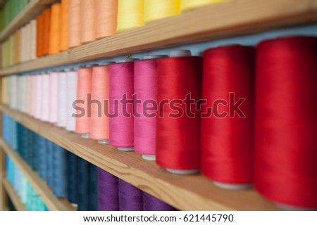 Multicolored cotton threads for sewing arranged by colors in store Zdjęcia stock ©