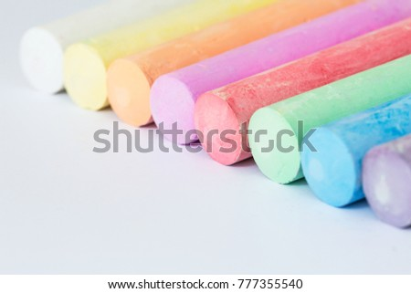 Multicolored crayons, pastel. Green, yellow, pink, purple, blue. Painted Pastels white blackboard #777355540