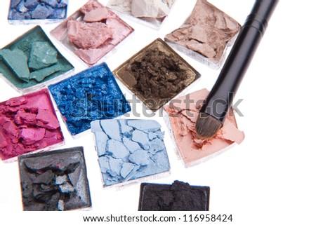 multicolored crushed eyeshadows with brush isolated on white background