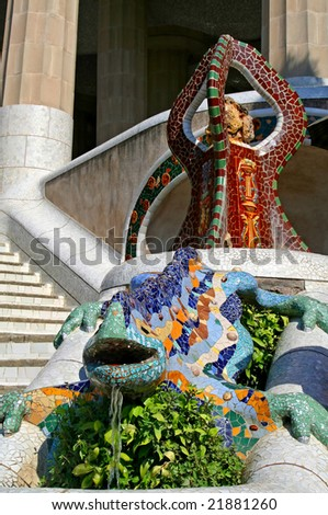 Multicolored dragon with ornamental brown tripod at Guell park, Barcelona, Spain