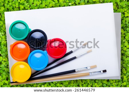 Multicolored drawing instruments (watercolor paints, paintbrush, blank sheet of paper) for create imagination over green clover background, creativity concept. Top view