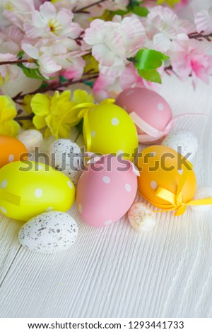 Multicolored easter eggs and flowers on white wooden background #1293441733