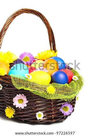 Multicolored Easter eggs in wicker basket isolated on white background