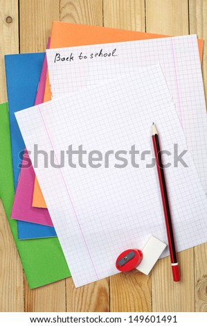 Multicolored exercise books, pencil and clean sheet on table