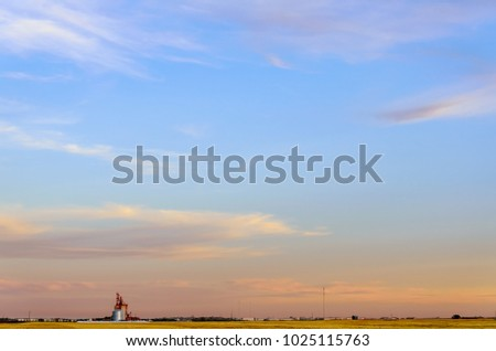multicolored, fluffy tender cirrus clouds, yellow field, elevator and silver barns for grain, timber, freight cars, white tower, radio and body towers, white buildings #1025115763