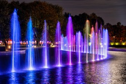 Multicolored fountain illuminated at night in Warsaw, Poland