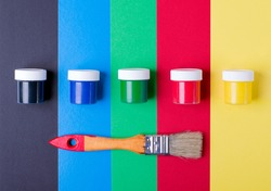 Multicolored gouache jars and paintbrush against the multicolored geometric background. Yellow, red, green, blue and black colors. Set for a painter