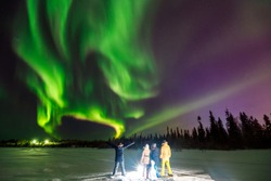 Multicolored green Violet vibrant Aurora Borealis Polaris, Northern Lights in night sky over winter Lapland landscape, Norway, Scandinavia. Concept travel team people. Soft focus blur effect