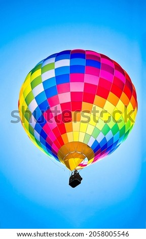 Multicolored hot air balloon in the sky. Hot air balloon with basket. Flying hot air balloon in sky. Colorful hot air balloon in sky