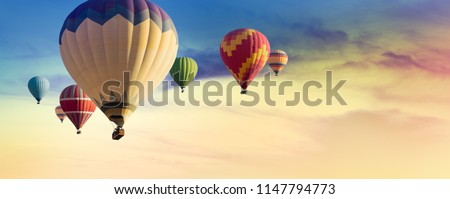 Multicolored hot air balloons at sunset sky for your billboard of a travel agency or wide banner, brigth colors and soft sun light. #1147794773