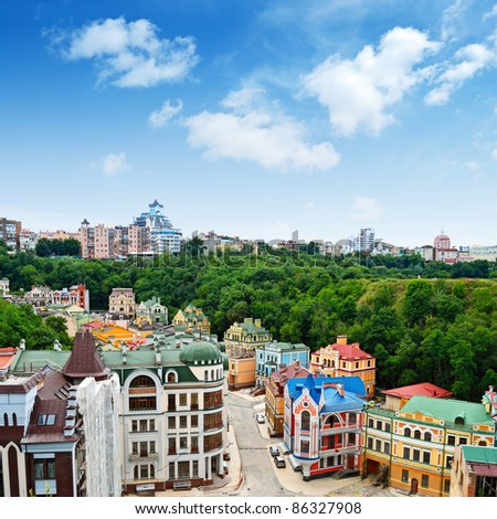 Multicolored houses among the green trees and blue sky. Panoramic view from the hill. Placed in Kiev, Ukraine almost in center of city.
