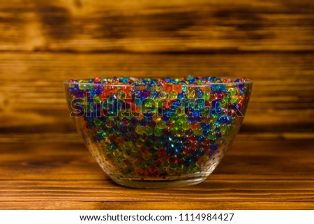 Stock Photo Multicolored hydrogel balls in glass bowl on wooden table