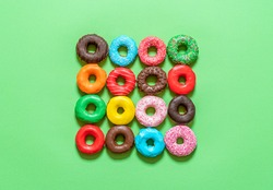 Multicolored icing doughnuts arranged symmetrically in a square on a green background. Homemade chocolate donuts decorated with sprinkles and colored icing.