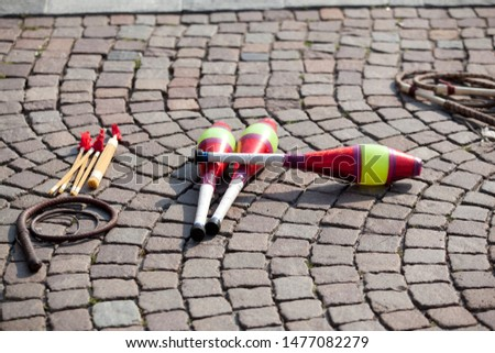 multicolored juggling stick on a cobbled street in a soft backlight