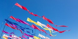 Multicolored kites in the form of bright ribbons on pillars, fluttering in the blue sunny sky in windy weather. Banner