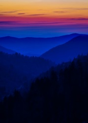 Multicolored layered mist depicted during a sunset in the Great Smoky Mountains