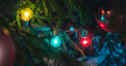 Multicolored light bulbs.Vintage, luxury lamp glowing on Xmas tree.Festive mood.Garland of lamps or glass lantern,the glow of light bulbs,decoration. Xmas decor. Holiday, Decorative string lights.