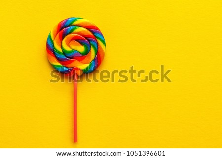 multicolored lollipop on yellow background, view from above. copy space.