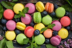 Multicolored macarons with blueberries and mint leaves close-up