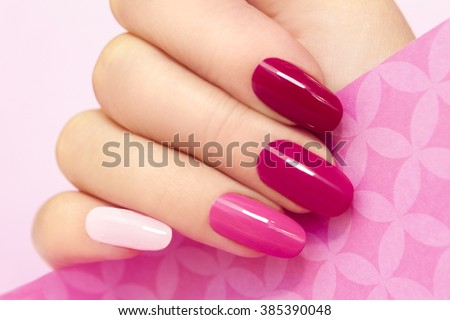 Multicolored manicure with different shades of pink nail Polish on women\'s hand.