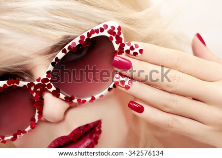 Multicolored manicure with red and white nail Polish decorated with rhinestones in the shape of hearts.