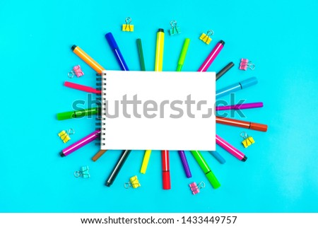 Multicolored markers, markers, paper clips and notebook on blue background Flat lay Top view Back to school, education, various stationery concept