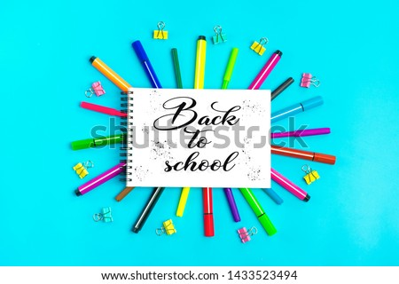 Multicolored markers, markers, paper clips and notebook on blue background Flat lay Top view Text back to school, education, various stationery concept