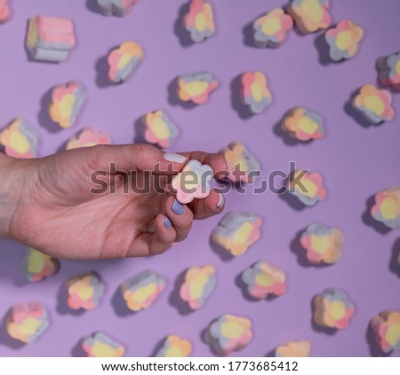 multicolored marshmallows in a woman's hand on a purple background